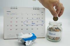 Eine Hand, die eine Münze in ein Glasgefäß gefüllt wird mit den beschrifteten Münzen einsetzt, reisen stockbild