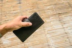 Eine Hand, die eine schwarze lederne Geldbörse hält Stockfoto