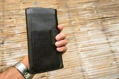 Eine Hand, die eine schwarze lederne Geldbörse hält Lizenzfreie Stockfotos