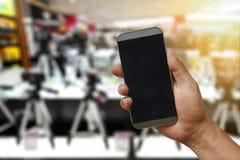 Eine Hand, die Smartphone auf unscharfem Kamerashopspeicher hält Stockbilder