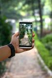 Eine Hand, ein Mobile und ein Bild in ihm Lizenzfreie Stockfotos