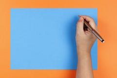 Eine Hand, eine Feder und ein farbiges Papier Lizenzfreies Stockbild
