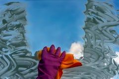 Eine Hand in einem Handschuh wäscht das Fenster lizenzfreie stockbilder