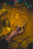 Eine Hand füllt eine kleine Schale mit gelbem Curry-Pulver Lizenzfreie Stockfotos