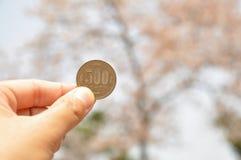 Eine Hand hält die 500-Yen-Münze Stockbilder