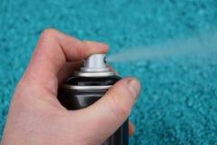 Eine Hand hält ein desodorierendes Mittel kann auf einem blauen Hintergrund Lizenzfreies Stockfoto