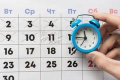 Eine Hand hält einen kleinen Wecker, im Hintergrund ist ein Kalender mit dem Tag markiert und den Wortferien stockfotos