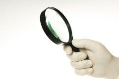 Eine Hand im weißen Handschuh, der eine Lupe auf einem weißen Hintergrund hält Lizenzfreie Stockfotos