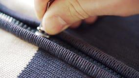 Eine Hand macht Reißverschluss zu und öffnet eine Wolljacke oder eine Wollstrickjacke stock video footage