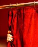 Eine Hand mit dem gemalten Finger nagelt das Anhalten eines roten Duschvorhangs stockfotos