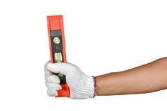 Eine Hand mit dem Schutzhandschuh, der orange Plastikgeistniveau hält Stockbilder