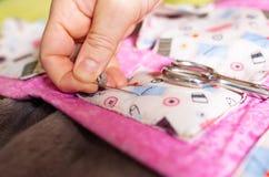 Eine Hand mit der Muffe, die eine Nadel in einen Stoff haftet stockfoto