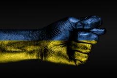 Eine Hand mit einer gemalten Ukraine-Flagge zeigt eine Feige, ein Zeichen des Angriffs, Widerspruch, eine Debatte auf einem dunkl lizenzfreies stockfoto