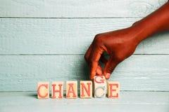 Eine Hand schlägt einen hölzernen Würfel mit den Wörtern ändern in die Wortmöglichkeit leicht Stockfotos