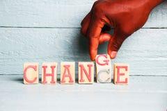 Eine Hand schlägt einen hölzernen Würfel mit den Wörtern ändern in die Wortmöglichkeit leicht Lizenzfreies Stockbild