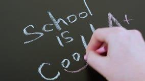 Eine Hand schreibt mit Kreide auf eine Tafelaufschriftschule ist kühl, zurück zu dem Schulkonzept stock video footage