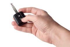 Eine Hand und ein Auto befestigen den Knopf, lokalisiert auf weißem Hintergrund Lizenzfreie Stockfotografie