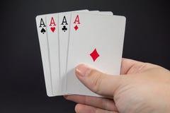 Eine Hand, welche die vier Asse von Spielkarten hält Lizenzfreie Stockfotografie