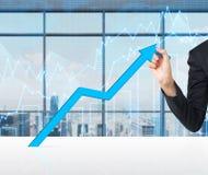 Eine Hand zeichnet einen wachsenden blauen Pfeil Lizenzfreie Stockfotos