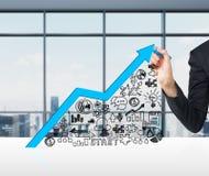 Eine Hand zeichnet einen wachsenden blauen Pfeil als Konzept des Erfolgs im Geschäft Stockbilder