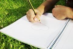 Eine Hand zeichnet Herz im Park Schließen Sie herauf Schuss Lizenzfreies Stockfoto