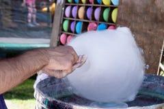Eine Handverpackung eine Zuckerwatte auf einem Stock in einer Zuckerwattemaschine stockfotografie