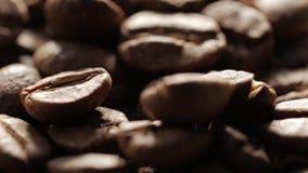 Eine Handvoll Braun, Röstkaffeebohnen auf Rausschmisshintergrund der Leinwand, Abschluss oben, Rotation stock footage