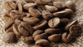 Eine Handvoll Braun, Röstkaffeebohnen auf Rausschmisshintergrund der Leinwand, Abschluss oben, Rotation stock video footage