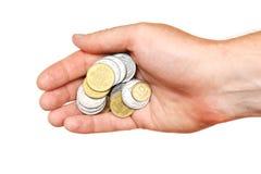 Eine Handvoll Münzen in der Palme einer Hand, lokalisiert Lizenzfreie Stockfotos