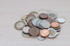 Eine Handvoll Münzen von verschiedenen Ländern, von Farbe, von Würde und von Größe stockfoto