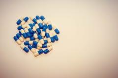 Eine Handvoll Pillen Kapselmedikationen weiß und blauer Medikament stockfotos