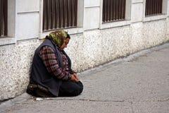 Eine heimatlose Frau bittet um Geld in der Straße Lizenzfreie Stockfotos