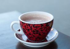Eine helle rote und schwarze Schale Kakao auf einer Holztischoberfläche Stockbild