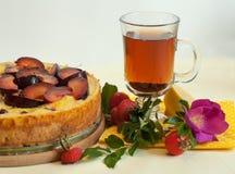 Eine helle Zusammensetzung mit einer Fruchttorte, einer Glastasse tee, einem frischen Hund rosafarben und Hüften Lizenzfreie Stockbilder