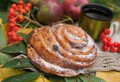 Eine helle Zusammensetzung mit einer Schale starkem schwarzem Tee, süßem Brötchen mit Rosinen, Aschbeeren, Äpfeln und buntem Herb Lizenzfreie Stockfotografie