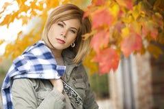 Eine herrliche blonde Frau, die einen hell farbigen Fallbaum bereitsteht Stockbild