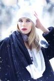 Eine herrliche blonde Frau mit blauen Augen draußen im Schnee Stockbilder