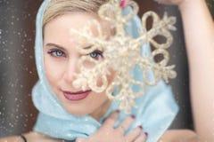 Eine herrliche blonde Frau mit einem blauen Schal, der eine Goldschneeflocke vor ihrem Gesicht im Schnee hält Lizenzfreie Stockbilder