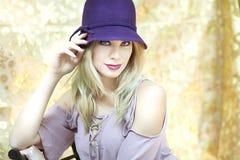 Eine herrliche blonde Frau mit einem hellen purpurroten Hut Stockfotografie