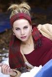 Eine herrliche blonde Frau mit einem roten Plaidschal um ihren Kopf im Winter Stockbilder