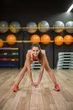 Eine herrliche Frau mit dem perfekten Körper, der das Ausdehnen auf einen Turnhallenhintergrund tut Aerobes, Eignungs- und Bodybu Stockbild