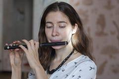 Eine herrliche junge Frau, welche die Flötenpiccoloflöte sitzt und spielt stockfoto
