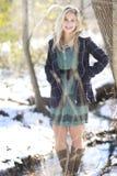 Eine herrliche lächelnde blonde Frau, die im Wald im Winter mit einem Knickentenkurzschlusskleider- und -Plaidmantel steht Stockfotografie