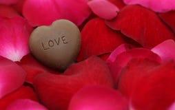 Eine Herzschokolade auf Hintergrund des rosafarbenen Blumenblattes Stockfotografie
