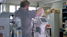 Eine hintere Ansicht über einen Soldaten, der einen hohen Roboter zusammenbaut stock footage