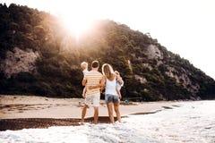 Eine hintere Ansicht der Familie mit zwei Kleinkindkindern, die auf Strand bei Sonnenuntergang stehen lizenzfreies stockbild