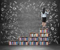 Eine hintere Ansicht der Frau, die pädagogische Ikonen auf dem enormen Kreidebrett zeichnet Eine Leiter gemacht vom Bücherregal Stockfoto
