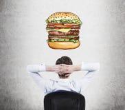 Eine hintere Ansicht des sitzenden entspannenden Mannes, der über Burger träumt Ein Schnellimbisskonzept Stockbild