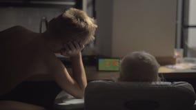 Eine hintere Ansicht eines Jungen und der aufpassenden Karikatur des Babys auf einer Tablette stock video footage