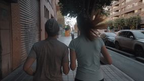Eine hintere Ansicht eines Paares, das entlang dem gepflasterten Bürgersteig rüttelt stock video footage